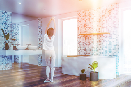 Rear view of woman in pajamas standing in comfortable bathroom with tiled walls, double sink and white bathtub. Toned image