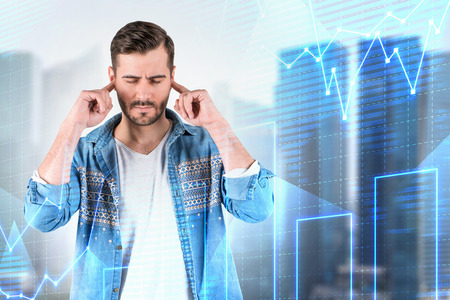 Stressed young man in casual clothes covering his ears standing over blurred cityscape background with graphs and diagrams interface. Concept of trading. Double exposure Stok Fotoğraf - 120821600