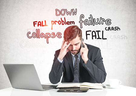 Concerned businessman talking on smartphone at office table near concrete wall with failure words written on it. Concept of crisis. Toned image