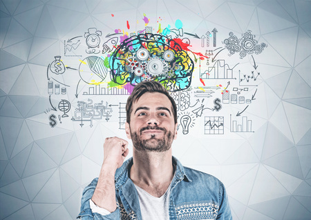 Smiling man with great idea standing near geometric pattern wall with colorful brain sketch and business plan on it. Concept of creative thinking Stockfoto