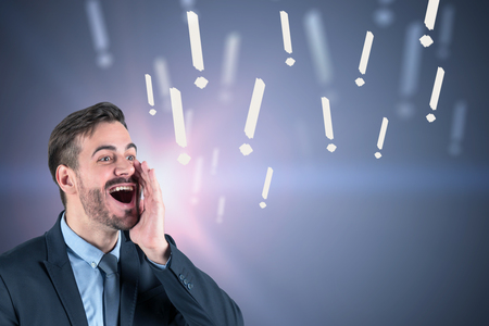 Bearded businessman telling news over gray wall background with question marks drawn on it. Toned image