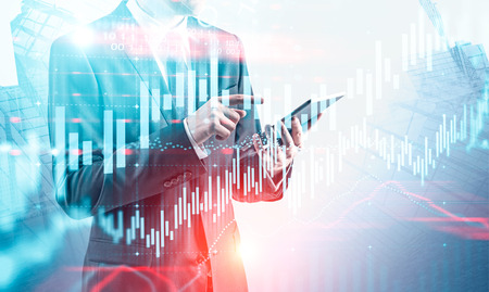 Unrecognizable young businessman using tablet computer over skyscraper background with double exposure of graphs. Concept of trading. Toned image