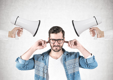 Young man in glasses and casual clothes covering his ears standing near concrete wall with two hands holding loudspeakers. Concept of disobedience and violence. Stock Photo