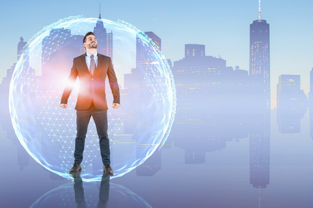 Portrait of confident young businessman standing with clenched fists over city background with planet hologram and looking upwards. Concept of success. Toned image