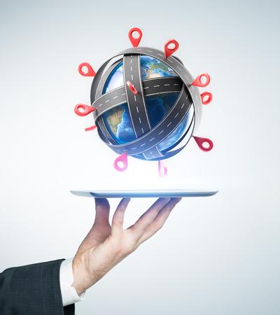 Ręka mężczyzny w garniturze trzymającego komputer typu tablet z modelem planety otoczony drogami ze znakami punktu kontrolnego. Pojęcie podróży. Stonowany obraz