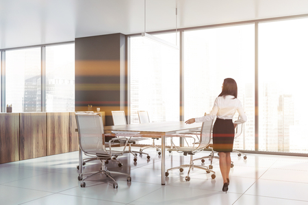 Rear view of dark haired businesswoman standing in modern office conference room with long meeting table and panoramic windows. Toned image