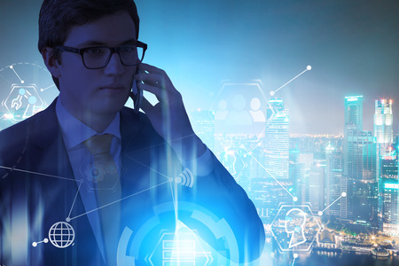 Handsome young businessman in glasses talking on smartphone over night city background with double exposure of GUI. Concept of hi tech in business. Toned image Stok Fotoğraf