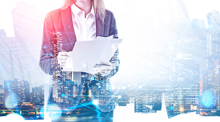 Unrecognizable businesswoman with documents standing over night city background with double exposure of network interface. Concept of hi tech. Toned image