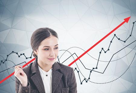 Durchdachte junge Geschäftsfrau mit Stift lächelnd stehend in der Nähe der grauen Wand mit wachsenden Diagrammen darauf gezeichnet.