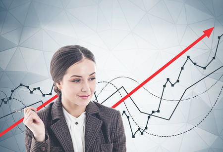 Thoughtful young businesswoman with pen smiling standing near gray wall with growing graphs drawn on it.