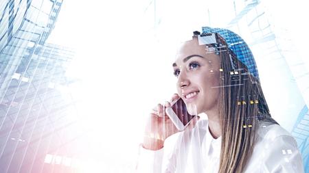 Sonriente a mujer joven con camisa blanca hablando por teléfono inteligente. Doble exposición de paisaje urbano abstracto. Concepto de comunicación empresarial. Imagen tonificada Foto de archivo
