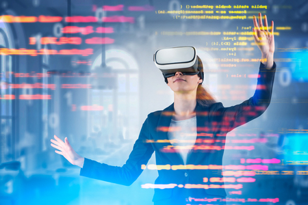 Young woman in virtual reality headset working with code over blurred office background. Concept of woman programmer and hi tech. Toned image double exposure Imagens