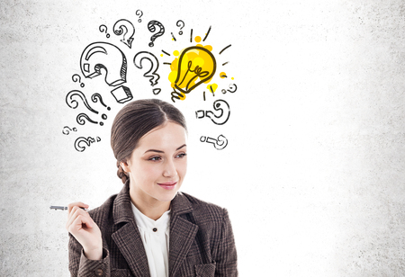 Thoughtful young businesswoman with pen smiling standing near concrete wall with question marks and lightbulb drawn on it. Concept of idea. Mock up