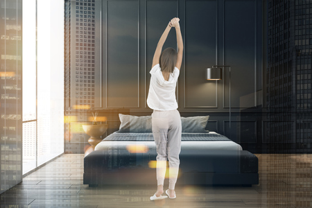 Woman in pajamas stretching in black bedroom interior with wooden floor and king size bed. Toned image double exposure Stok Fotoğraf