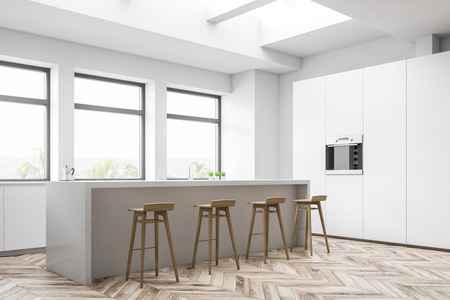 Corner of white kitchen with white countertops, white cupboard with built in oven and white bar with wooden stools. Three large windows with tropical view. 3d rendering Stock Photo