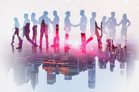 Silhouettes of business people shaking hands and communicating over cityscape background with network hologram. Concept of telecommunication. Toned image double exposure