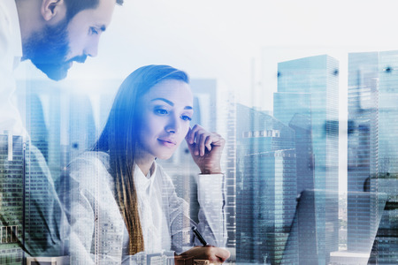 Inspired young businesswoman and confident businessman working at office table. Double exposure of cityscape. Concept of discussion. Toned image double exposure