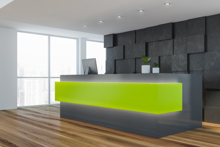Side view of green and gray reception table with computer on it standing in stylish office interior with gray walls, wooden floor and large windows. 3d rendering