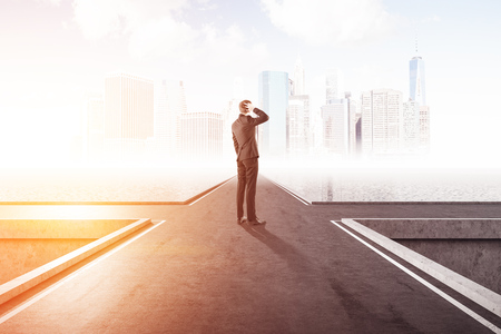 Rear view of confused young businessman standing on crossroad over city background. Concept of decision making. Toned image Stockfoto