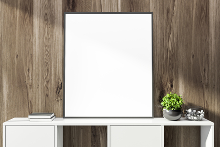 Blank mock up poster frame standing on white cabinet in room with dark wooden walls. Potted plant and bowl with pebbles. 3d rendering