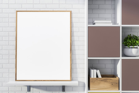 Blank mock up poster with wooden frame standing on white shelf in room with white brick walls and bookcase. Concept of advertising. 3d rendering Zdjęcie Seryjne