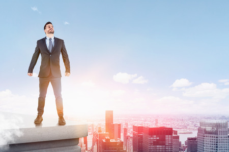 Portrait of confident young businessman standing with clenched fists on roof in city and looking upwards. Concept of success. Toned image
