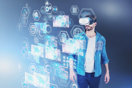 Bearded young man in casual clothes and virtual reality headset looking at digital interface with business images and internet icons. Toned image double exposure