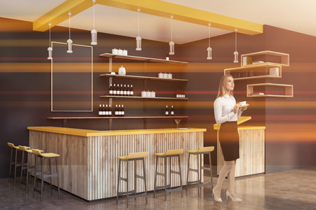 Blonde woman in suit standing in gray bar interior with concrete floor, yellow and wooden bar and shelves with bottles and pots. Toned image
