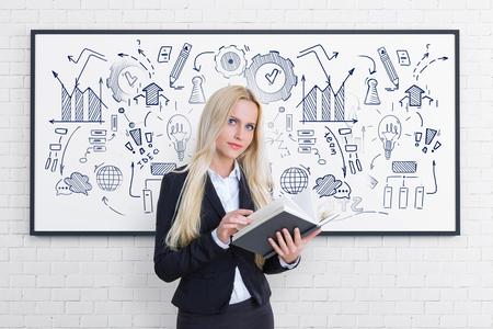 Bella donna bionda di affari con il libro in piedi vicino allo schizzo del business plan disegnato sulla lavagna. Concetto di start up e formazione aziendale