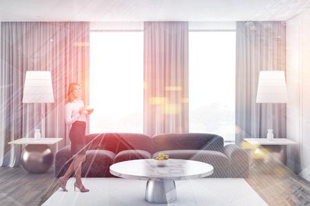 Sorridente imprenditrice bionda in piedi in un elegante soggiorno con pareti bianche, pavimento in legno, divano grigio e tavolino in marmo. Doppia esposizione dell'immagine tonica Archivio Fotografico