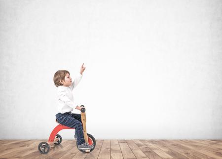 Porträt eines entzückenden kleinen Jungen in weißem Hemd und Jeans, der Dreirad fährt und nach oben zeigt. Betonwandhintergrund. Attrappe, Lehrmodell, Simulation