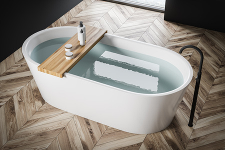 Top view of white bathtub with water and shelf with creams and shampoos standing in modern bathroom with wooden floor and black walls. 3d rendering Imagens
