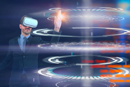 Bearded young man in virtual reality headset using futuristic HUD interface over dark blue background with blurred lines of code. Toned image double exposure