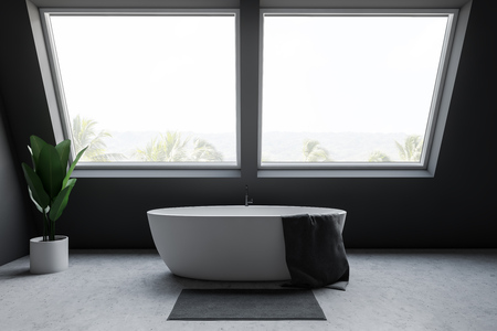 Interior of minimalistic attic bathroom with gray walls, concrete floor, white bathtub with towel on it standing under large windows with tropical view. 3d rendering