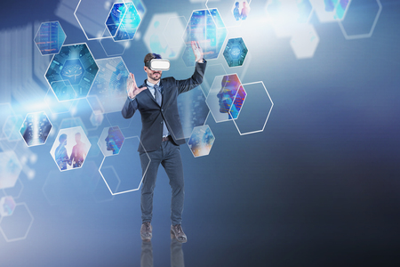 Serious young man in VR headset working with business images. Concept of hi tech in business and engineering. Toned image double exposure. Elements of this image furnished by NASA