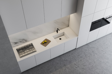 Top view of modern kitchen with gray and marble walls, concrete floor, white countertops with built in sink and stove and white cupboards with ovens. 3d rendering