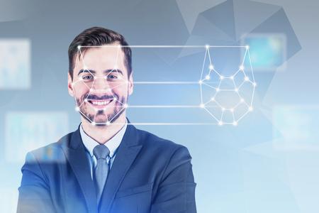 Fröhlicher junger Mann im Anzug mit Gesichtserkennung und biometrischer Verifizierungstechnologie. Konzept der Sicherheitsüberprüfung und des maschinellen Lernens. Verschwommener grauer Hintergrund. Doppelbelichtung Standard-Bild