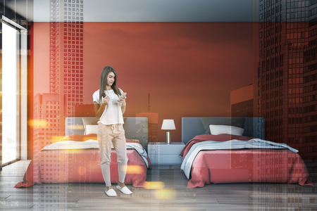 Young woman with smartphone and coffee standing in modern red bedroom interior with loft window and two beds with bedside table between them. Toned image double exposure Reklamní fotografie