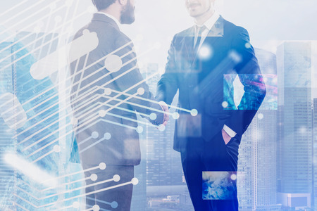 Two business leaders shaking hands over cityscape background with circuit and infographics interface. Concept of fintech and partnership. Toned image double exposure