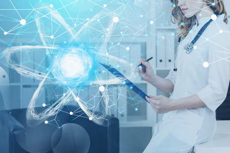 Unrecognizable woman scientist working in white office with double exposure of glowing atom hologram. Concept of scientific research and hi tech. Toned image