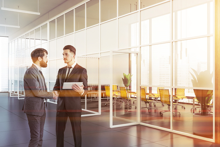 Two young businessmen shaking hands in modern office lobby with meeting room interior behind glass doors. Concept of partnership. Toned image Standard-Bild - 122937883