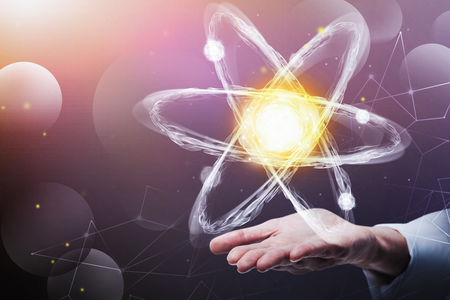 Hand of man in white shirt holding glowing atom hologram. Concept of scientific research and modern technology. Toned image double exposure