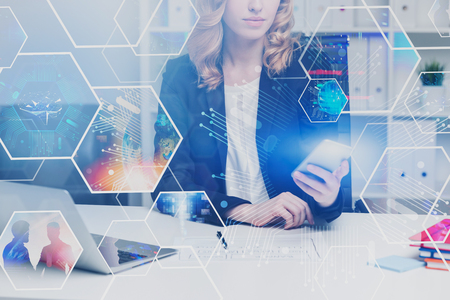 Woman in suit working with phone and laptop in office. Double exposure of digital screen with business images. Concept of hi tech and engineering. Toned image. Elements of this image furnished by NASA