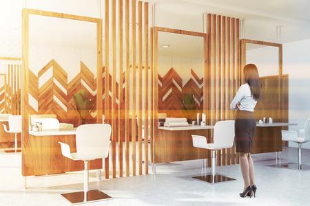 Jeune femme aux cheveux noirs debout dans un salon de beauté ou un salon de coiffure avec murs en bois, grands miroirs et tables et chaises blanches avec serviettes et crèmes. Concept de beauté et de santé. Image tonique Banque d'images