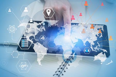 Hand des Mannes mit Tablet-Computer auf Bürotisch mit Doppelbelichtung des globalen Business-Infografik-Hologramms. Konzept von Big Data und High-Tech im Geschäft. Getöntes Bild