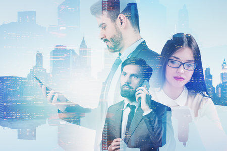Thoughtful young woman in glasses, bearded calm businessman on phone and their serious colleague looking at smartphone over cityscape background. Toned image double exposure