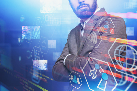 Confident man in suit standing with crossed arms with double exposure of digital business interface. Concept of hi tech and big data. Toned image