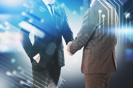 Unrecognizable businessmen shaking hands over blurred background with circuit interface. Concept of technological startup and partnership. Toned image double exposure