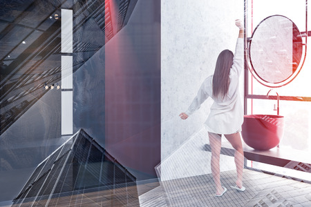 Rear view of woman in pajamas standing in luxury bathroom corner with concrete, gray and marble walls, wooden floor, red sink and shower. Toned image double exposure