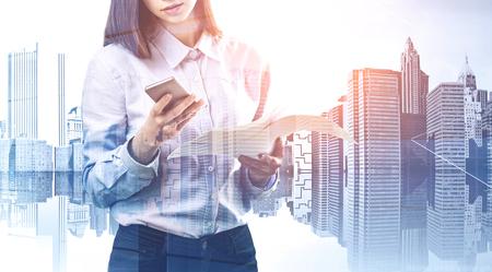 Irriconoscibile giovane imprenditrice in piedi con telefono e documenti sullo sfondo del paesaggio urbano. Concetto di comunicazione. Doppia esposizione dell'immagine tonica